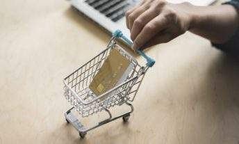 Woman's hand holding mini shopping cart with credit card